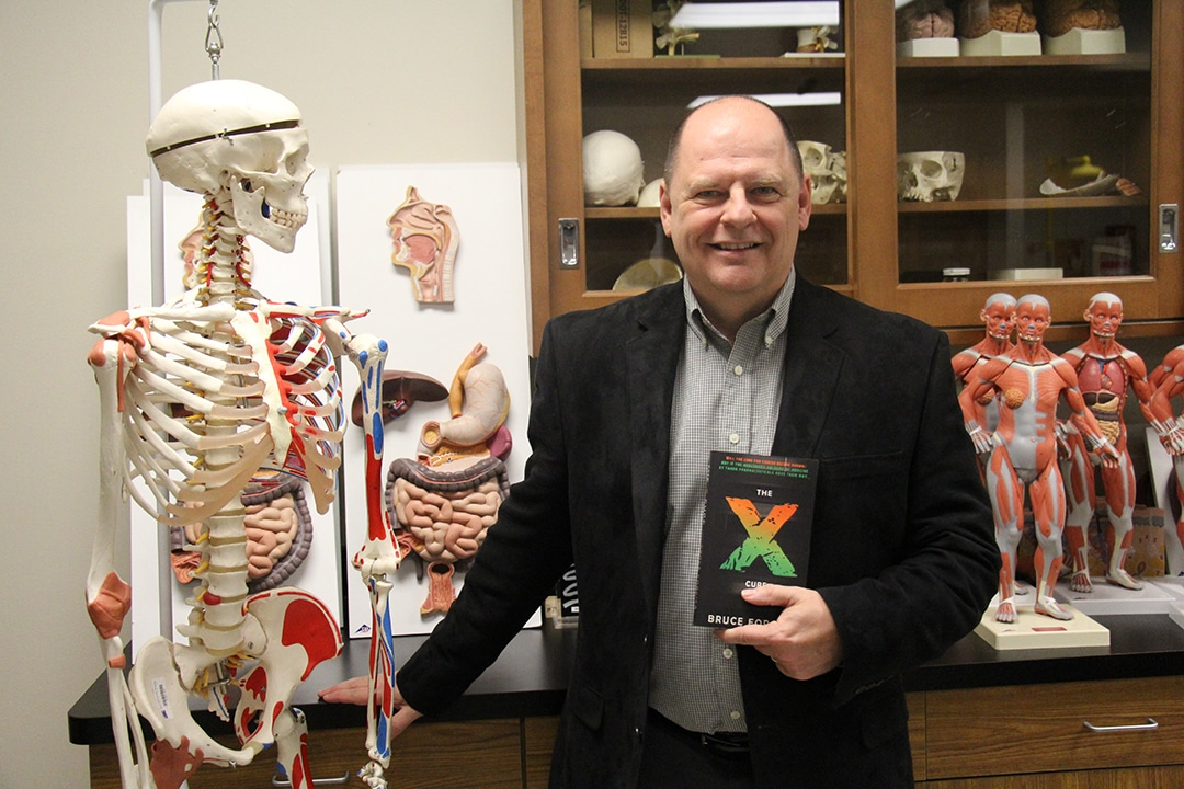 Moraine Park instructor, Bruce Forciea with book and skeleton