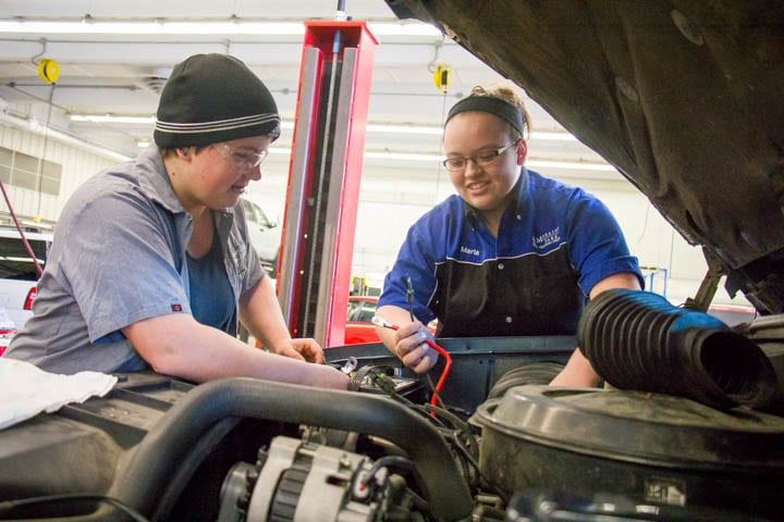 Two female automotive students working on engine
