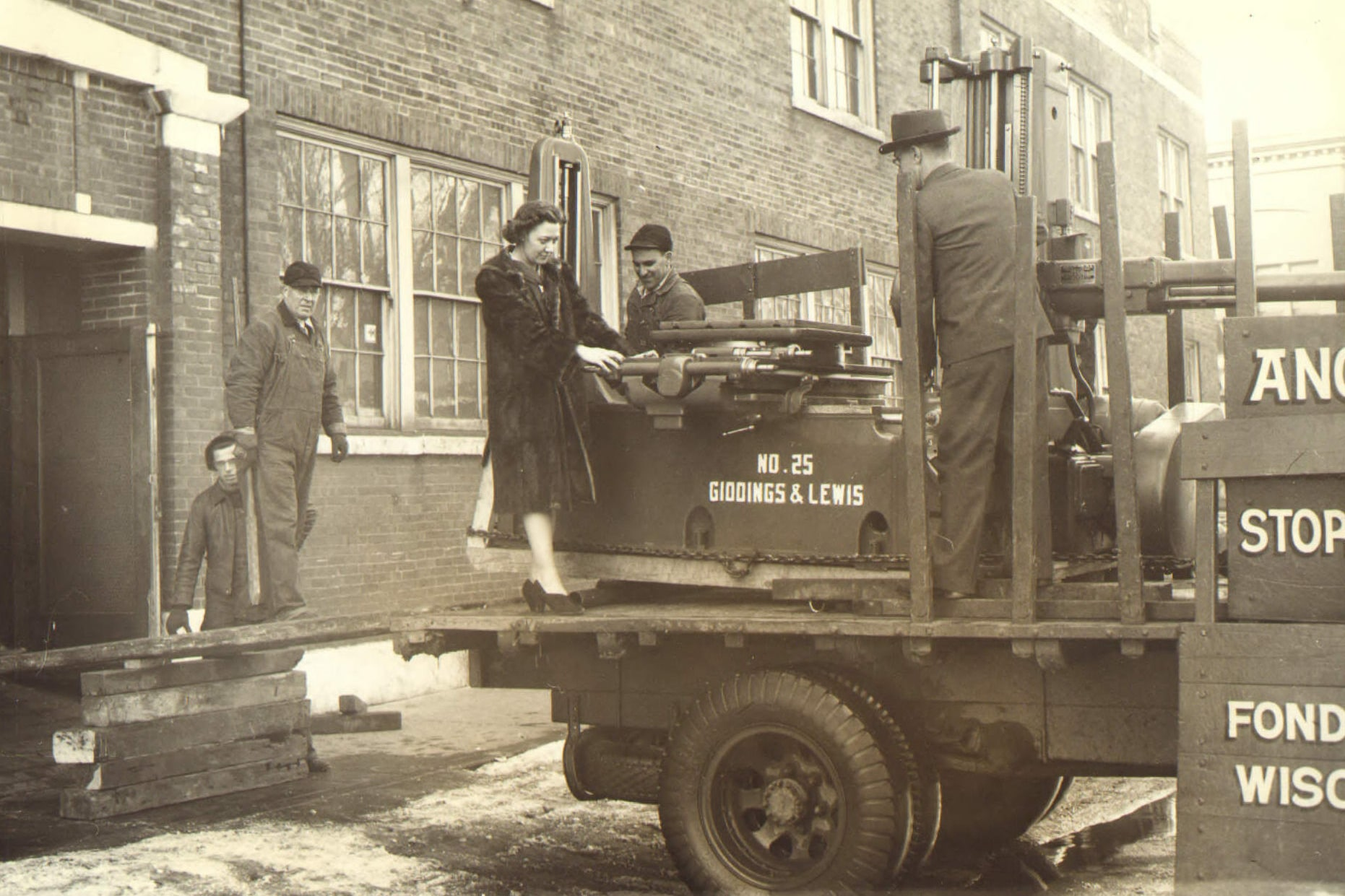 Vintage black and white photo of truck and people by Giddings and Lewis