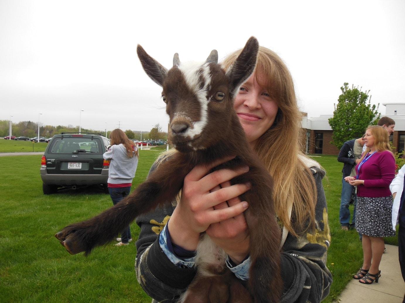 Female holding baby goat