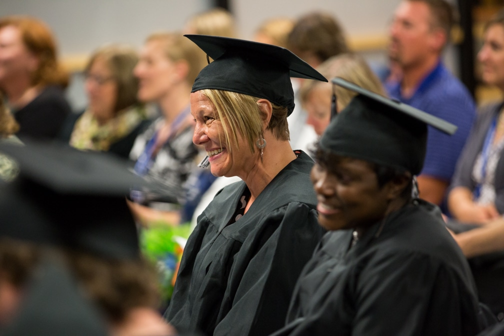 Female gradaute smiles at Moraine Park GED-HSED graduation ceremony
