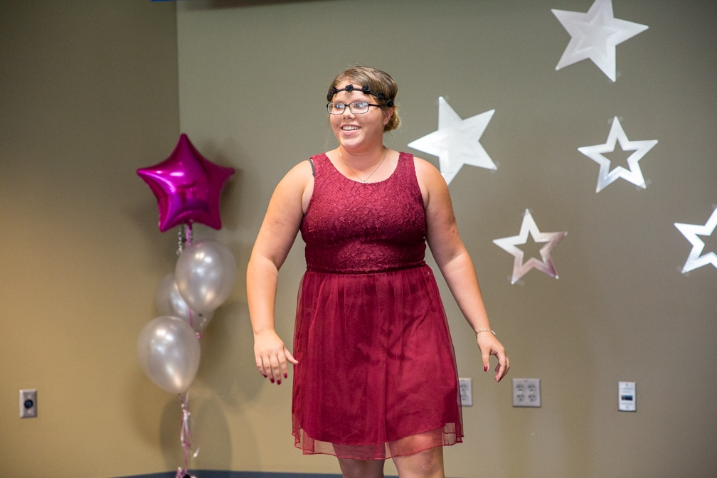 Female in short red dress posing for Moraine Park Technical College Cosmetology Fashion Show