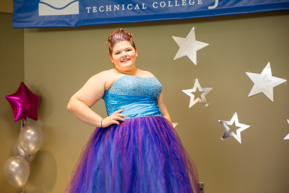 Female in purple and blue dress posing for Moraine Park Technical College Cosmetology Fashion Show