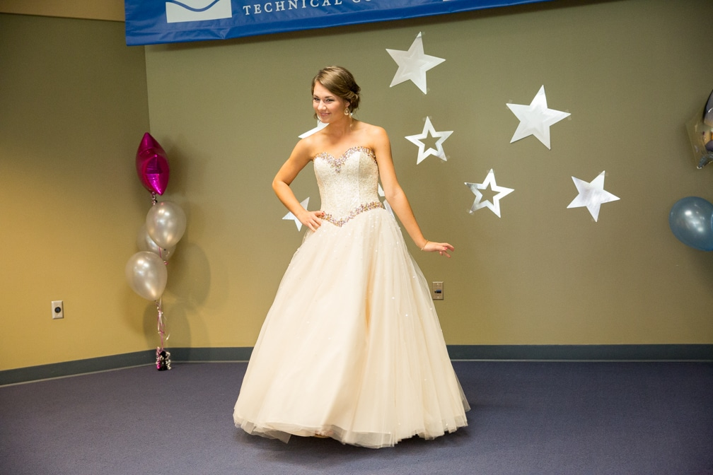 Female in long full cream colored dress posing for the Moraine Park Technical College Cosmetology Fashion Show