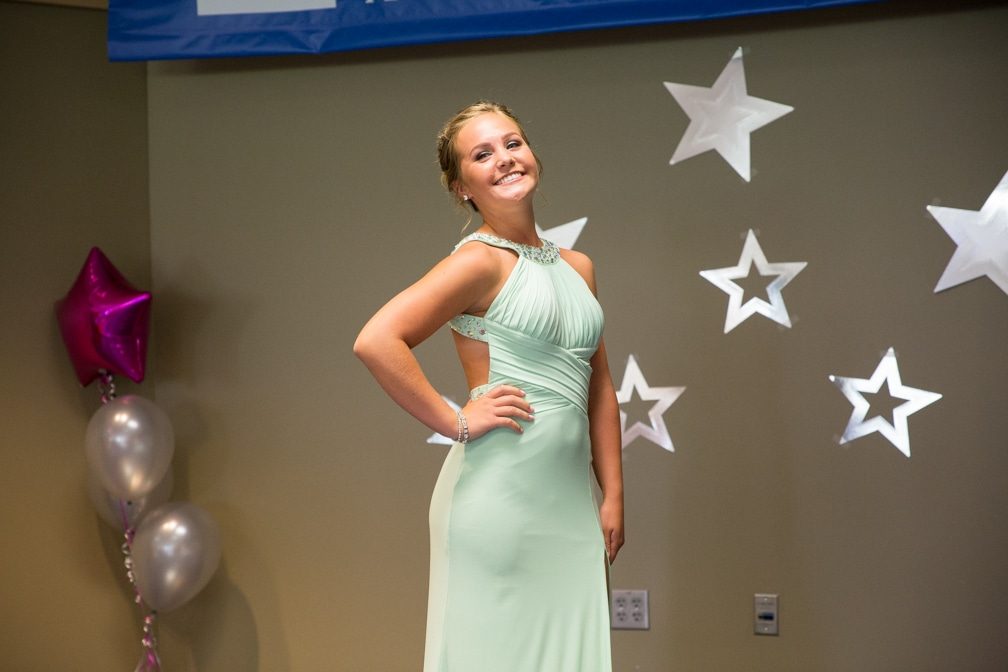 Female in long mint green dress posing for the Moraine Park Technical College Cosmetology Fashion Show