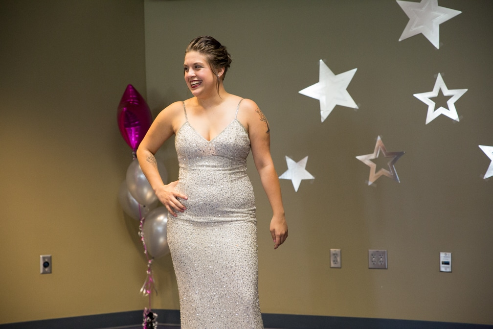 Female in long sparkling silver dress posing at the Moraine Park Technical College Fashion Show