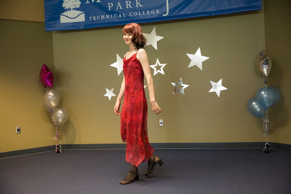 Female in long red dress posing for Moraine Park Technical College Cosmetology Fashion Show