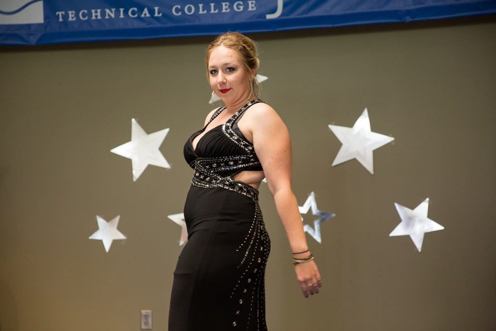 Female in long black dress posing at the Moraine Park Cosmetology Fashion Show
