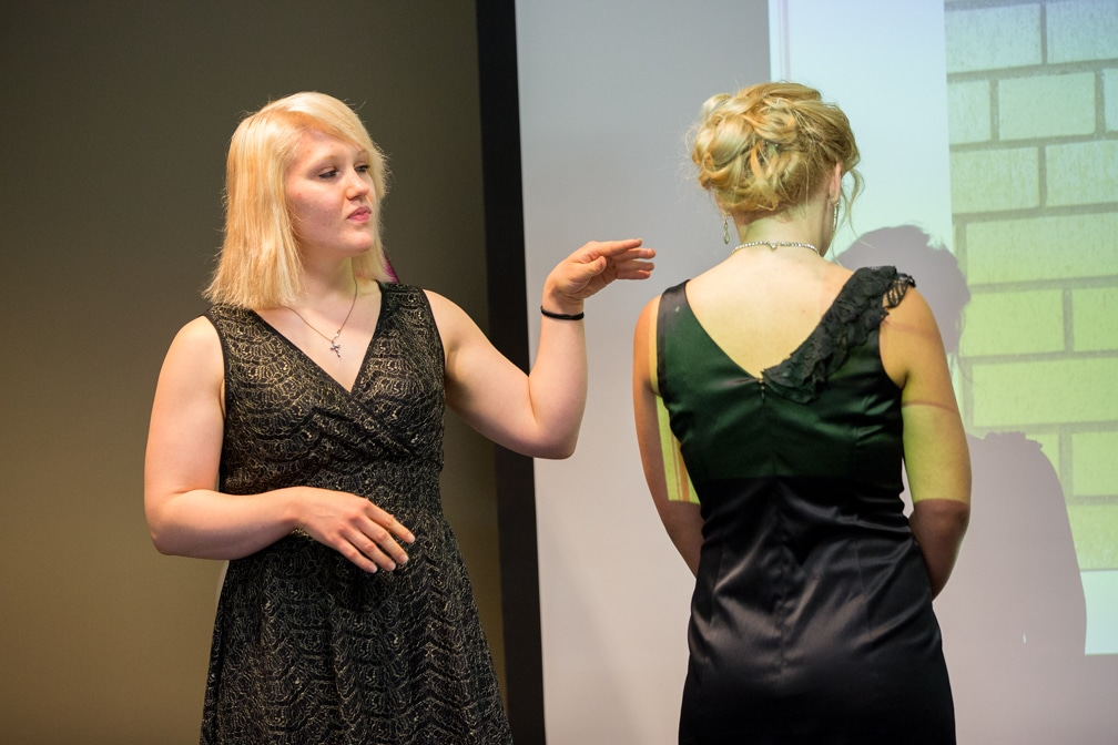 Two females, one describing the hairstyle of the other for the Moraine Park Technical College Cosmetology Fashion Show