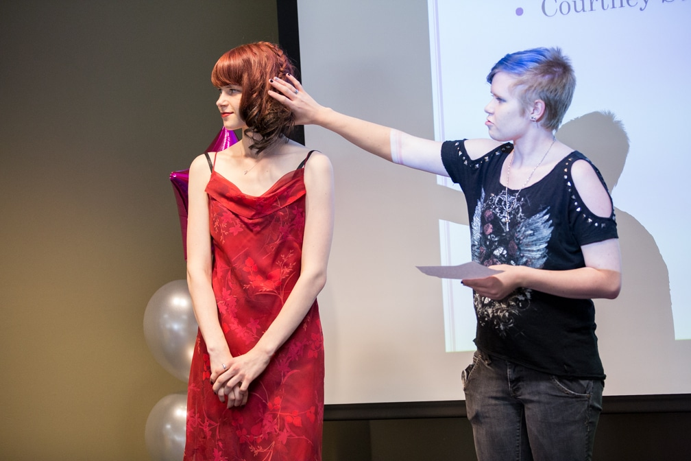 Two females, one describing the other's hairstyle for the Moraine Park Technical College Cosmetology Fashion Show
