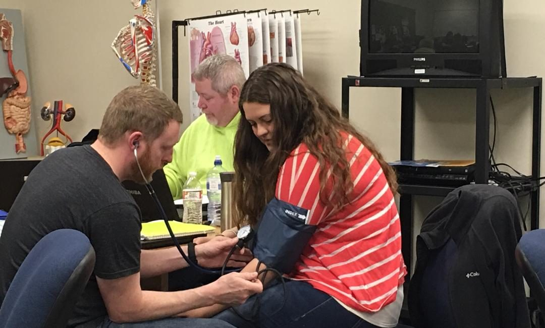 Moraine Park medical assistant student taking blood pressure of another student