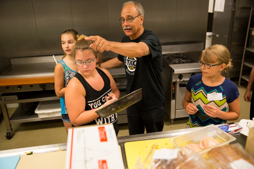 Culinary instructor pointing girls where items are