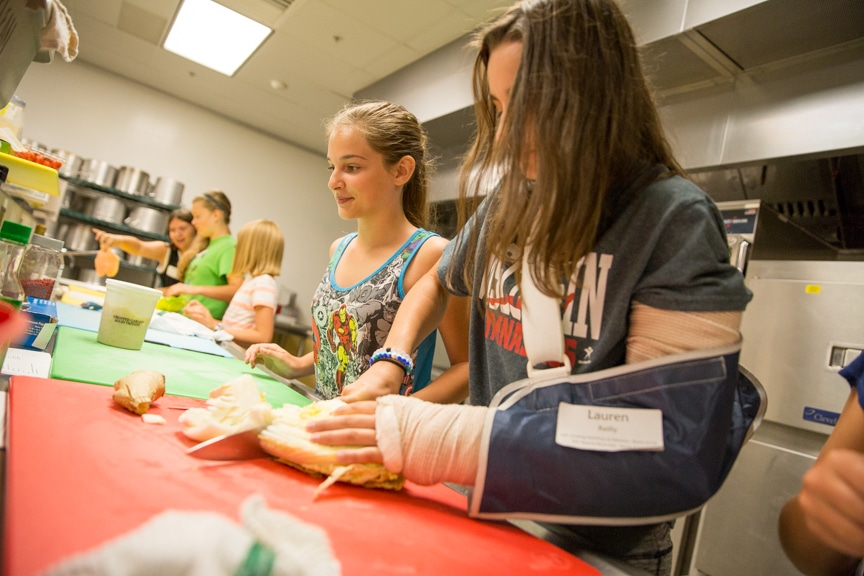 Girls cutting bread at TKC event