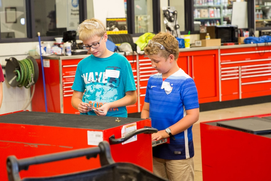Two boys looking in tool drawer in auto lab