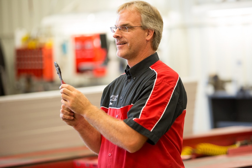 Moraine Park automotive instructor holding up a wrench