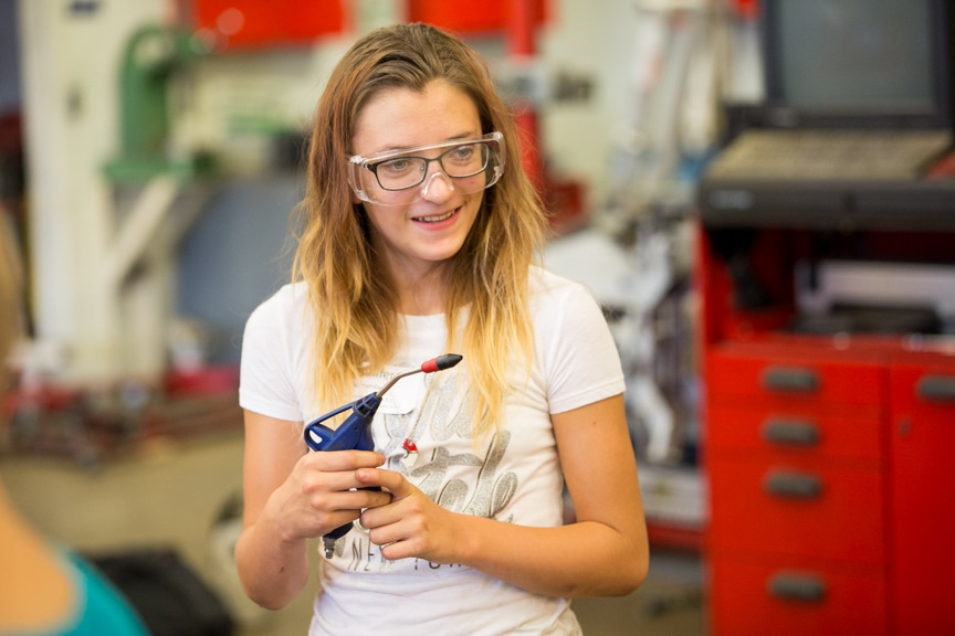 Girl working in automotive lab at Boys working on computers at Tech Knowledge College event