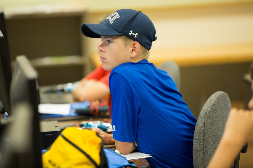 Boy looking intently at instructor at Boys working on computers at Tech Knowledge College event
