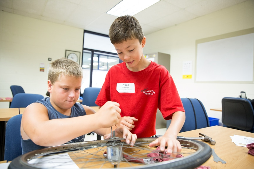 Two boys working on bicycle wheel at Tech Knowledge College event