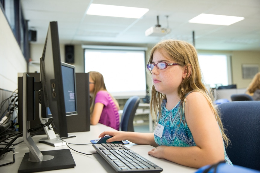 Young girl working on computer at Tech Knowledge College event
