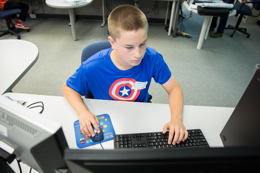 Young boy working on computer at Tech Knowledge College event