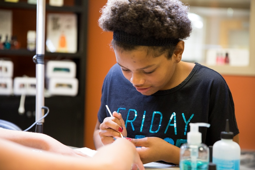Young girl getting manicures at Tech Knowledge College event