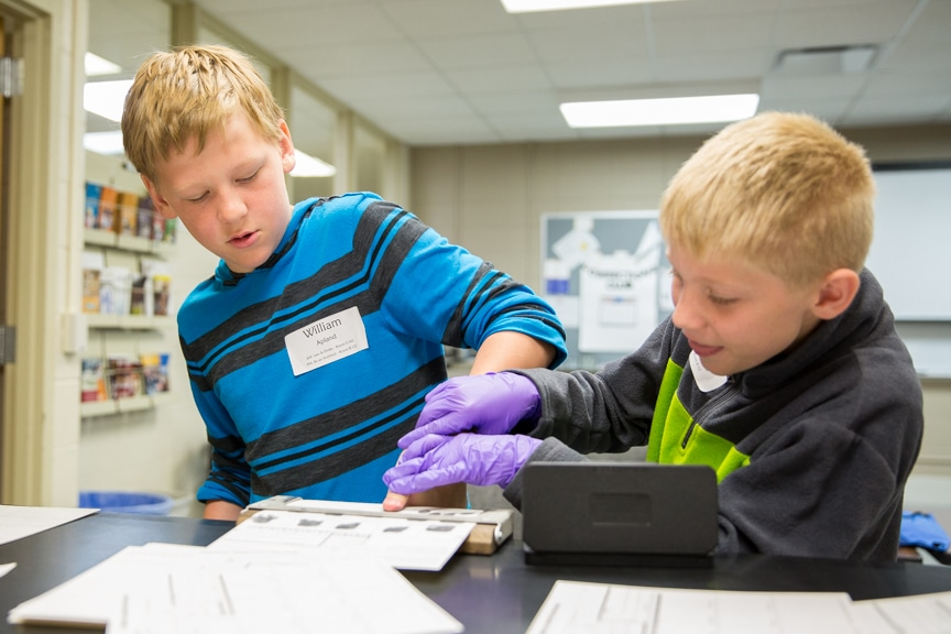Young boys taking finger prints at Tech Knowledge College event