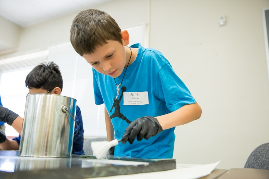 Young boy dusting for finger prints at Tech Knowledge College event
