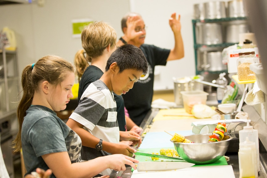 Culinary Instructor Ron Speich, teaching 6 - 8 graders how to prepare a dish in the kitchen