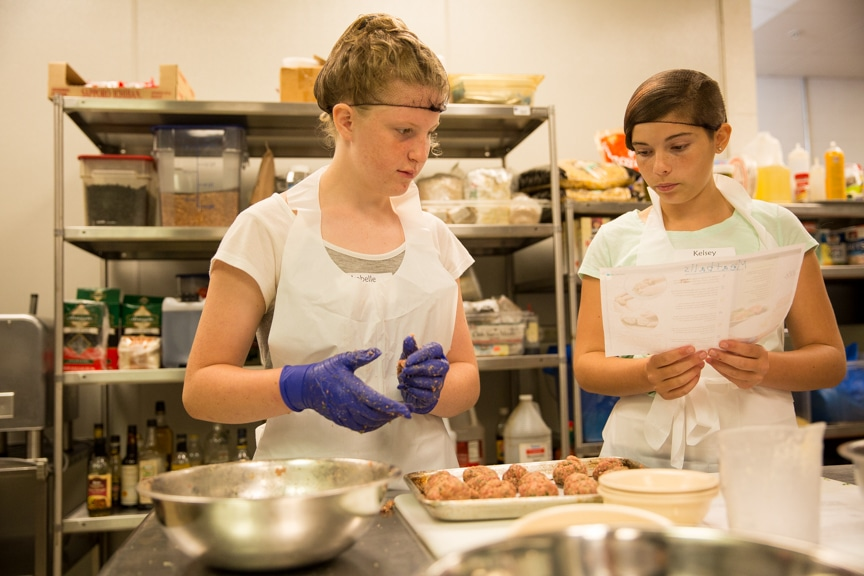 Two girls baking in Tech Knowledge College event at Moraine Park