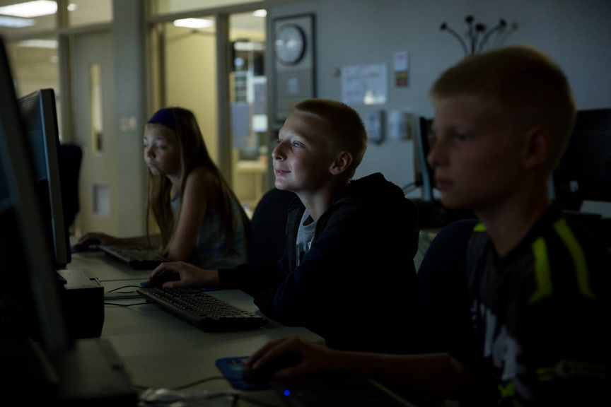 One female and two male 8th graders working on computer