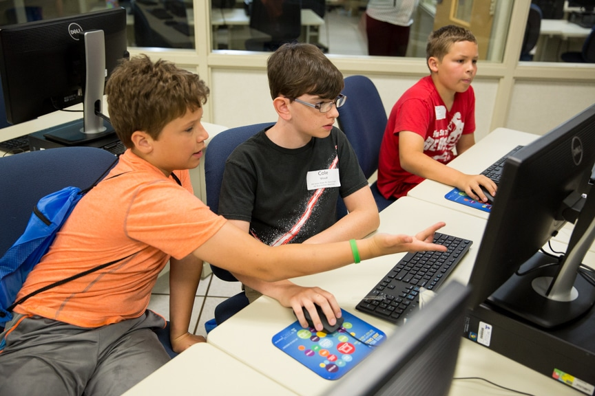 Three male 8th graders working on computer