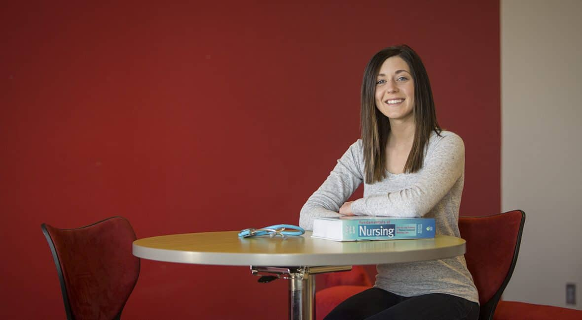 female Moraine Park nursing student sitting at table with book