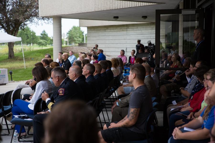 Crowd listening at picnic tables at 9-11 Memorial Rededication