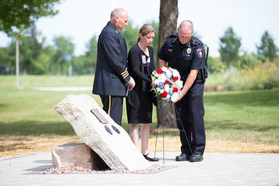 Two officers and female placing wreath at 9-11 Memorial Rededication