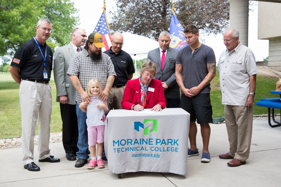 Moraine Park president Bonnie Baerwald signing a document at 9-11 rededication ceremony