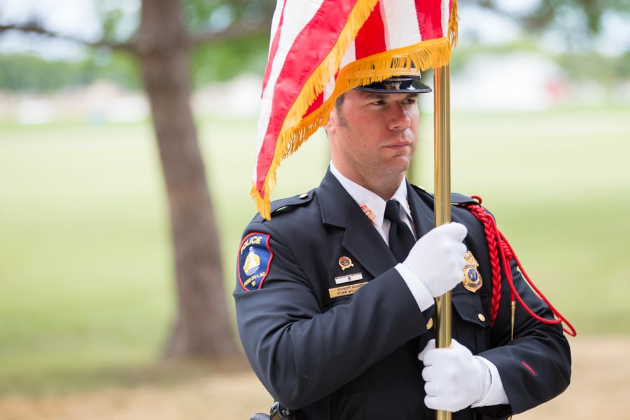 Officer holding flag at 9-11 Memorial Rededication at Moraine Park