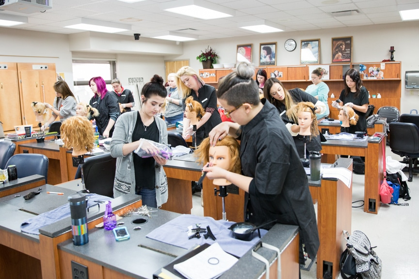 female cosmetology student parting mannequin hair