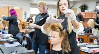 female cosmetology student coloring mannequin hair