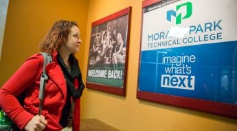 female student looking at new moraine park logo sign on wall