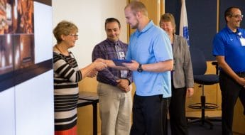 Moraine Park Business Instructor Ann Lemke shaking hands wtih students at TACT 3 summer cohort ceremony