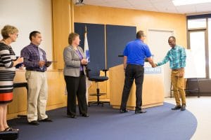 Moraine Park Business Instructor Jeff Stueber shaking hands wtih students at TACT 3 summer cohort ceremony