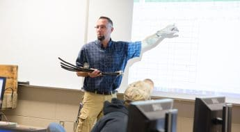 instructor mark wamsley points to screen in front of class