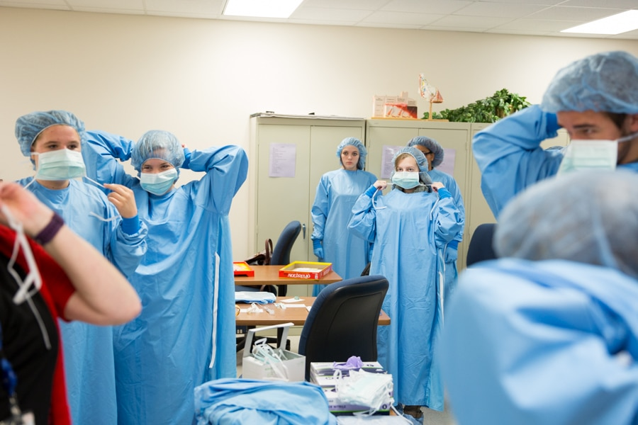 middle school students putting on surgical gowns at moraine park