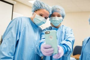 middle school students take selfie in surgical gown and masks