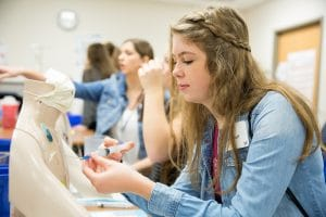 female middle school student examines item at healthcare event