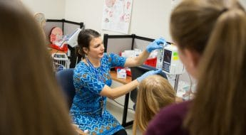 instructor demonstrates healthcare activity to middle school students