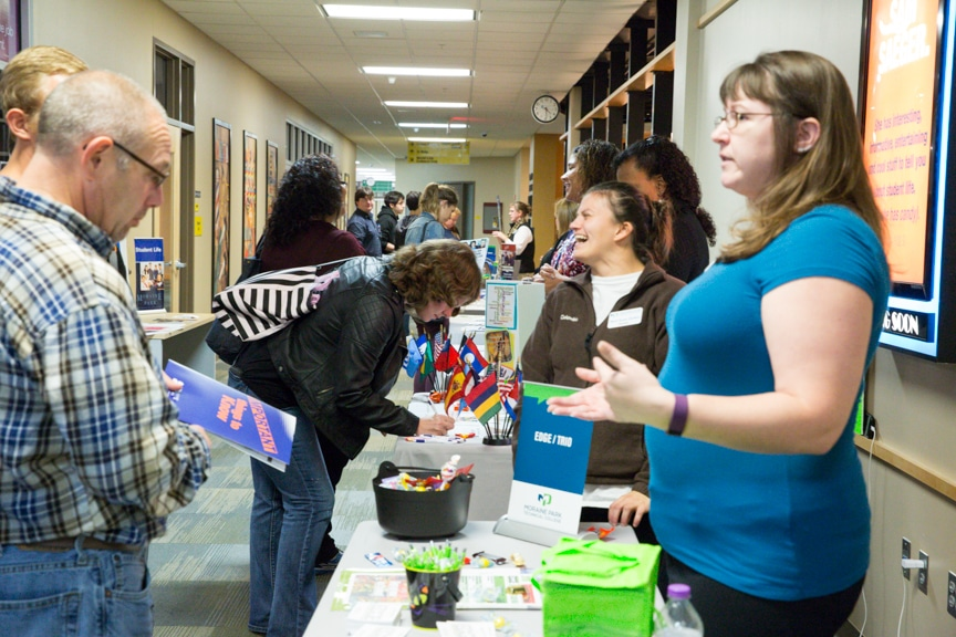 women at table help guests at moraine park