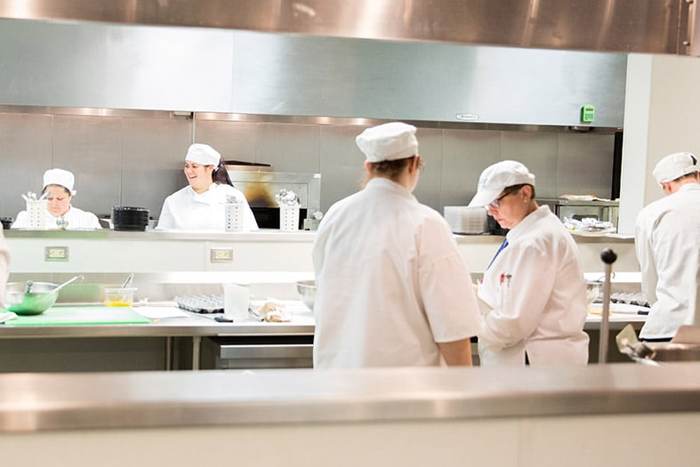 Moraine Park culinary instructor Lois Zingsheim and students in kitchen