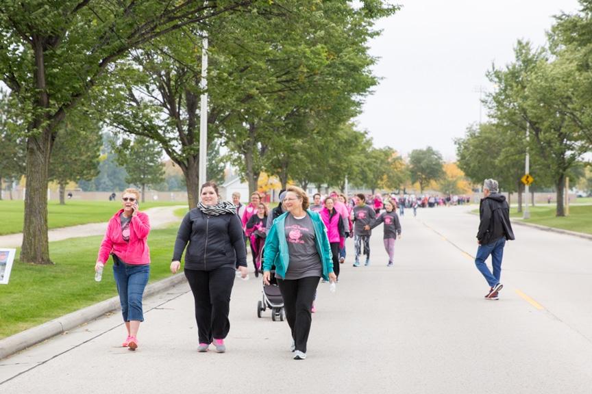 crowd walks on street during moraine park great pink pumpkin walk