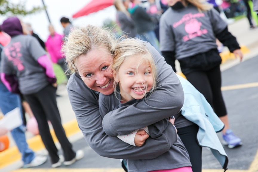 woman hugs child at moraine park pink pumpkin race